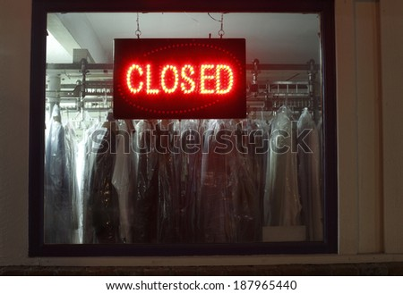 Closed sign in dry cleaners window - stock photo