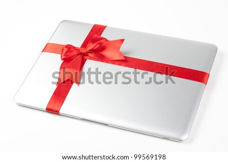 closed silver laptop gift with red ribbon isolated on white background - stock photo