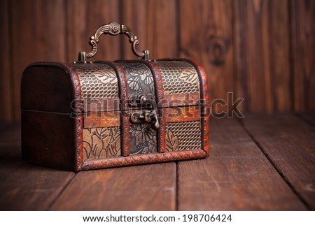 closed treasure chest standing on wooden table - stock photo