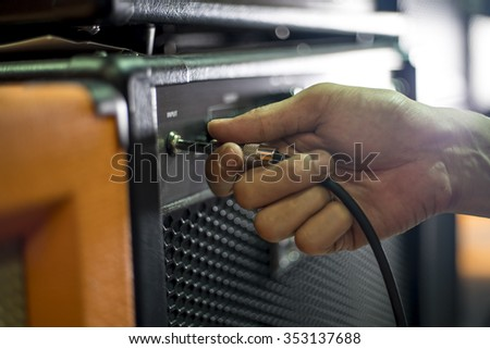 Closed up hand holding jack plug-in to the guitar amplifier, shallow DOF, selected focus - stock photo