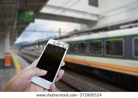 Closed up hand of man touch screen, Train station background - stock photo