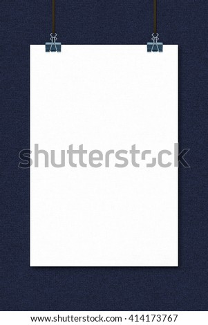Closed-up hanging blank poster on blue jeans texture background with black binder for product presentations or portfolios.