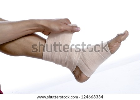 Closed up man putting bandage on his injured feet