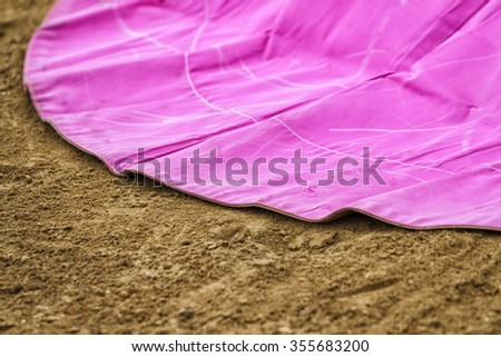 closed up of a cape of fighting of cloth of the canvas of pink color on the sand