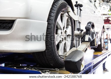 Closed up of an auto wheel that is undergoing wheel alignment - stock photo