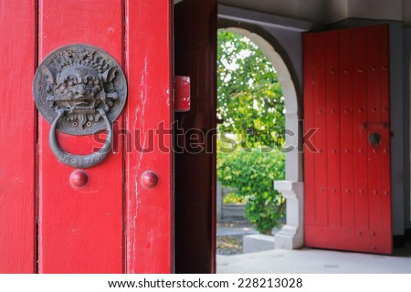 Closed Up of Vintage Chinese Lion Door Knocker on Red Wooden Door. The Lion Hold A Mini Sword in Its Mouth. In The Background is Another Arch Door Opened. - stock photo