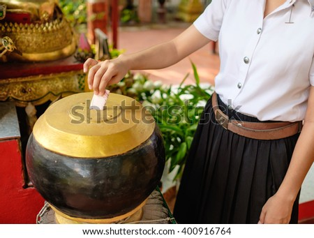 closed up to young thai girl student in uniform donate money for buddhism temple in Thailand - stock photo