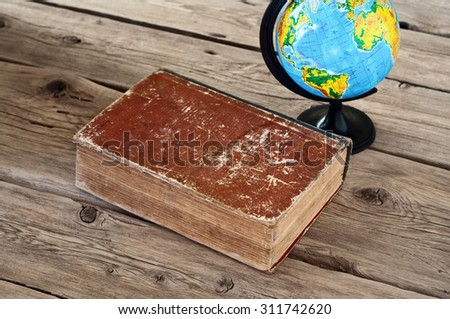 Closed vintage book with a globe on a wooden table close up. Top view. Copy space. Free space for tex - stock photo