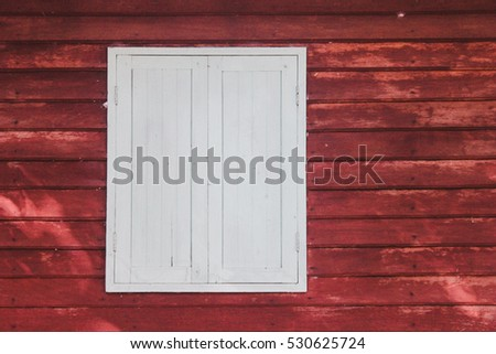 Closed white wood window of the red wooden house.