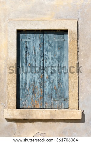 Closed Window with Blue Shutter / Detail of a closed old window with blue weathered shutter on grey wall - Italy - stock photo