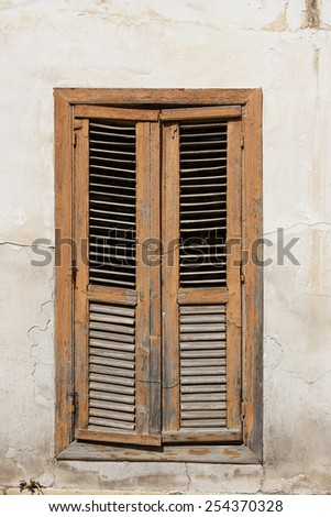 Closed window with old wood shutter - stock photo