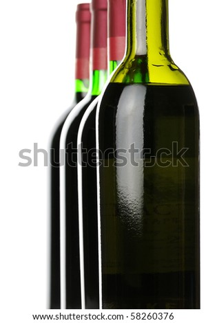 Closed wine bottles in row on white background. - stock photo