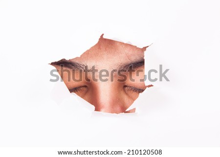 closed women eyes through paper hole - stock photo
