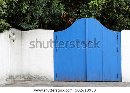 Closed wooden gate decorated with white plaster wall