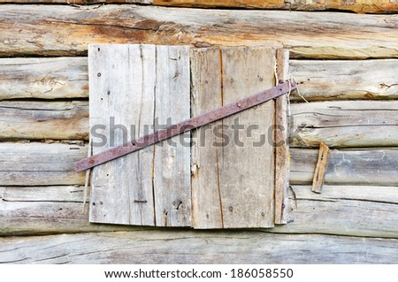 Closed wooden shutters on the log wall.