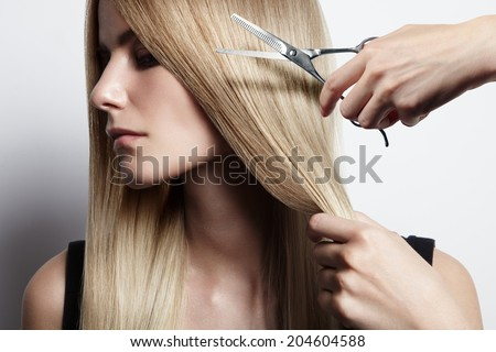closeiup portrait of a woman with a hand holding scissors