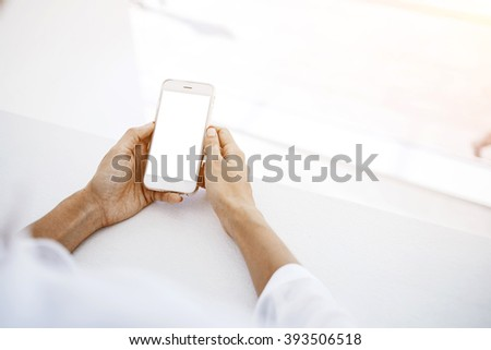 Closely image of a woman`s hands is holding mobile phone with empty mock up copy space screen for advertising text message or promotional content. Female is reading on cell telephone financial news - stock photo