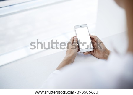 Closely image of a woman`s hands is holding mobile phone with mock up copy space screen for your advertising content.Hipster girl is watching video in web via cell telephone during her recreation time - stock photo
