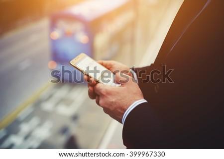 Closely of businessman is searching information on web page via mobile phone while is standing in office interior with city view.Male entrepreneur is typing text message in internet via cell telephone - stock photo