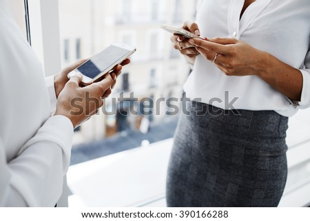 Closely up of women lawyers are using their mobile phones during break between court session. Two young female managers are searching needed information for work in internet via cell telephones - stock photo