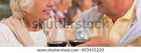 Closer shot of elder couple looking at each other with glasses of red wine