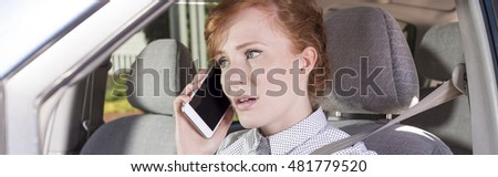 Closer shot of red-haired woman driving a car with a mobile phone in her hand