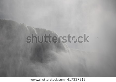 Closer view, misty shot of the powerful flow of water over niagara falls. - stock photo