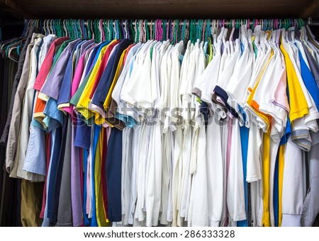 Closet full of clothes hanging on hangers. - stock photo