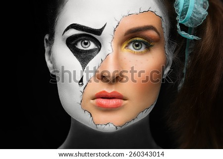 Closeuo portrait of beautiful young woman with Pierrot mask on her face