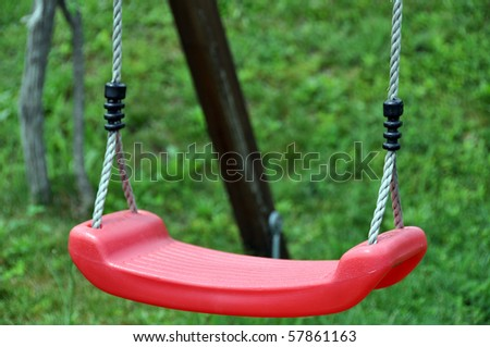 Closeuop of red childrens swing in green grass