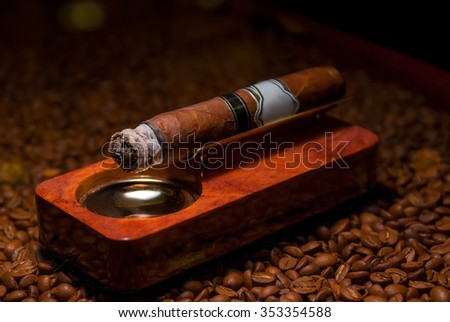 closeup a cigarette in the ashtray on the wooden coffee beans - stock photo