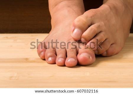 Closeup man itchy feet uses his stock photo 607032116 for Hardwood floors hurt feet