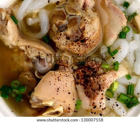 Closeup a noodle soup of bowl: in rice long noodle with pork leg cutting, pepper and onions - stock photo