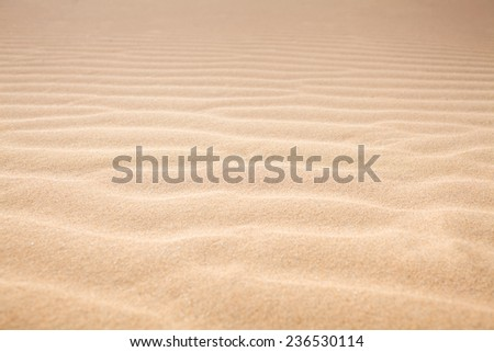 Closeup a wavy pattern on the sand/ Sand texture - stock photo