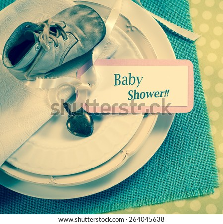 Closeup Above View of a Vintage Baby Shoe and Teething Ring and Note Card on table place setting.  Change the text, words, copy to your desire.  Square old fashion, retro trendy, faded instagram  - stock photo