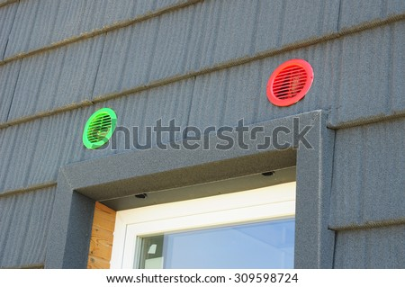 Closeup. AC vent on the side of house and windows ventilation systems. Energy efficient ventilation systems. - stock photo