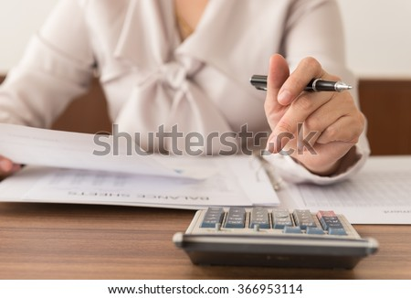 Closeup accountant women check the numbers on the balance sheet. Concept of accounting,accountant,bookkeeping,calculated,audit. - stock photo