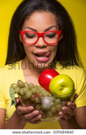 Closeup African AMerican woman with fruits. Beautiful african woman looking at fruits and smiling - stock photo