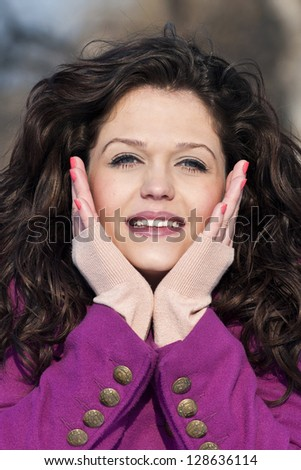 Closeup and details of a girl holding her face and smiling - stock photo