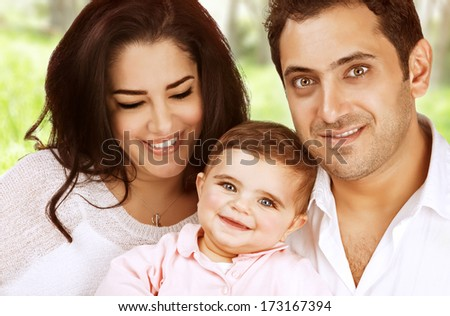 Closeup arabic family portrait spending time outdoors, young parents with little daughter in the park, love and happiness concept - stock photo
