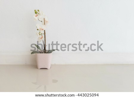 Closeup artificial plant with white flower on pink flower pot on blurred marble floor and white cement wall textured background , fake white orchid flower - stock photo