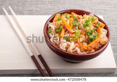 Closeup Asian dish of rice noodles and vegetable sauce in a small brown wooden bowl on a wooden stand