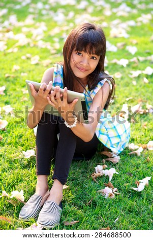 Closeup asian girl sitting on grass with tablet computer in the park - stock photo