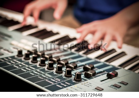 closeup audio mixer on hands playing the keyboard background,vintage color tone - stock photo
