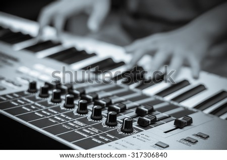 closeup audio mixer on hands playing the keyboard background,vintage color tone