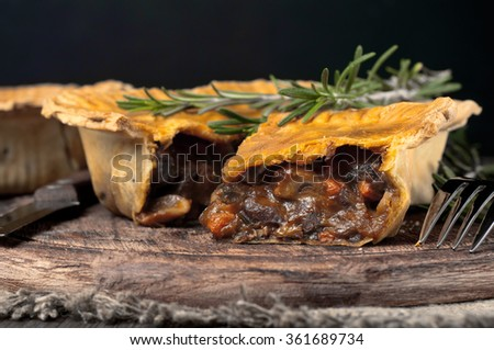 Closeup Australian meat pie on the wooden table with copy space, rustic style - stock photo