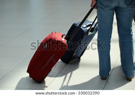 Closeup back view of female legs in jeans with red rolling suitcase standing in queue behind blue wheeled travel bag over airport terminal floor tile background, horizontal picture - stock photo