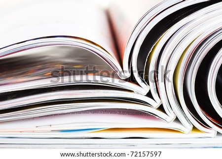 Closeup background of a pile of old magazines with bending pages - stock photo