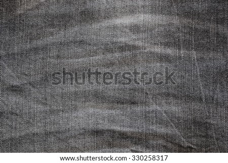 Closeup background photo of texture of Dark grey denim jeans textile