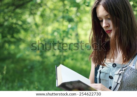 Closeup bbeautiful girl walking reading book on sunny summer day - stock photo